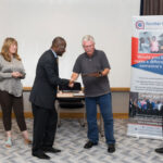 Joseph Ejoh receiving his Employee of the Year award from the Frontier Board